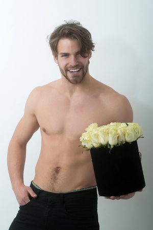 Smiling man with beard or sexy bodybuilder, athletic macho with fit, naked torso with fresh roses, flowers, in black present box on white wall. Holiday celebration and fitness