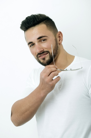 man with beard, young caucasian macho or model with stylish hair, haircut, holding fashionable vintage aviator sunglasses in hand on white background. Eye care and eyewear