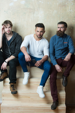 friends or men people sitting on wooden stairs on beige wall. Bearded caucasian male models with stylish hair in fashionable casual clothes. Beards fashion and hairstyles
