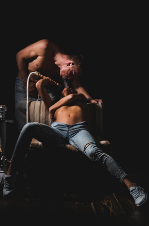 spirit and magic, love and relations, sexy couple, naked girl with bare chest in jeans on chair, handsome man with muscular torso, body smoking hookah, kalian as arabic tradition on black background