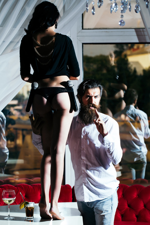 young couple of handsome bearded man hipster with long beard and pretty cute woman or girl with sexy legs and buttocks holding microphone or mic in restaurant with cocktail in glass near window Stock Photo