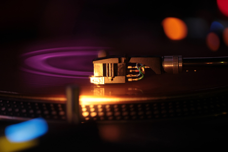 phono: Moving pickup or audio cartridge playing on retro vinyl disc on record player or turntable, phonograph device, with colorful bokeh lights on black background. Music and entertainment Stock Photo