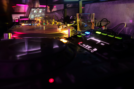 Professional dj equipment, record turntables and mixer with vinyl disc in night or dance club. Colorful neon lights on dark background. Nightlife, music, entertainment