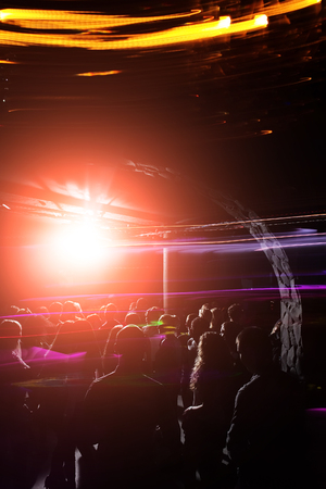 Young people with energy at party with abstract background of motion lights, music party celebration in night or disco club. Nightlife and entertainment