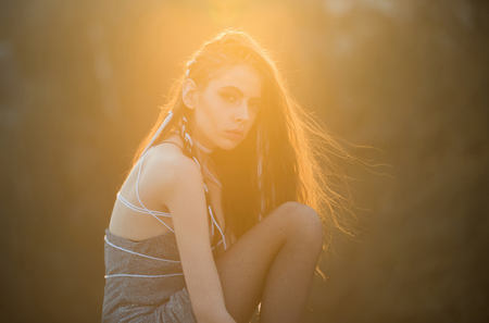 girl with long fashionable indie hairstyle, pretty woman has white rope in hair, makeup, piercing in nose in summer dress at sunset on natural background, boho, tribal style
