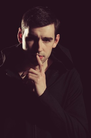 man or elegant handsome guy in stylish coat on black background, holding finger near mouth has thoughtful face, shady business