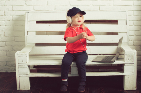 little boy or cute blonde child in headset listen music or audiobook, working on laptop, business and education
