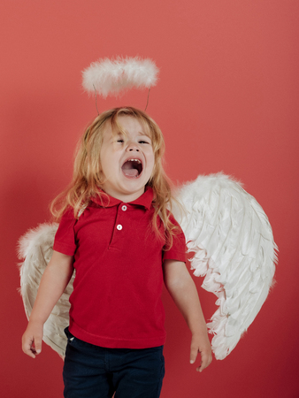 cupid on valentines day holiday, adorable little angel boy with white feather wings and halo, crying kid with sad face and blonde hair on red background