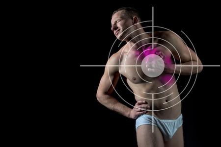 nackte brust: Mann mit Ziel auf der Brust hat Kummer auf schwarzem Hintergrund stehend, Ein Kerl mit nacktem Körper und muskulösen Oberkörper in weißen Hosen. Konzept mit Gesundheitswesen und Medizin, Kopie, Raum Lizenzfreie Bilder