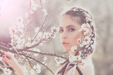cherry tree spring blossom, beautiful girl or woman portrait in flowers, young pretty female with fashion hair and makeup pose in blooming garden or summer park outdoor, skin care