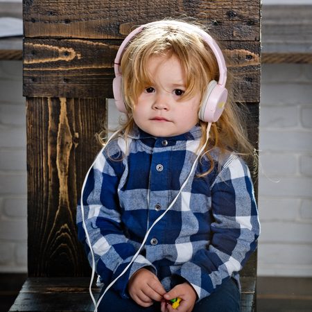 small baby boy in headset listen music or audiobook in fashionable checkered shirt on wooden chair has blonde hair