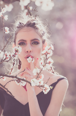 beautiful girl in spring park with flowers lifestyle portrait, happy woman with blooming cherry tree. Skin care and beauty. female in garden enjoying nature. Spring concept. Series.