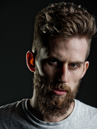 metrosexual: confidence and success, man or bearded young hipster has mustache and beard on serious face and fashionable hairstyle on grey background