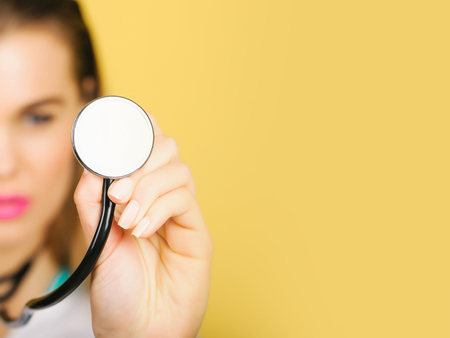 Modern stethoscope, medical acoustic device, with small disc resonator in female hand of blurred, pretty doctor or nurse, cute woman, girl on orange background. Healthcare and examination, copy space Stock Photo