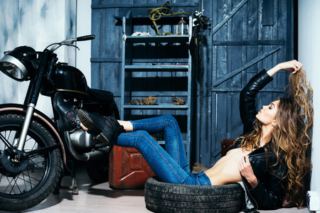 Sexy girl or pretty woman, stylish model with curly, blond, long hair in unbutton, erotic leather jacket lying in dirty, rubber tire on floor on motorcycle garage background. Wheel and vehicle service Stock Photo