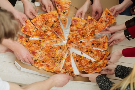 pizza and human hands taking delicious, cooked, big, fat dish, fast food, slices from delivery box package. Italian cuisine. Obesity and dietary problems