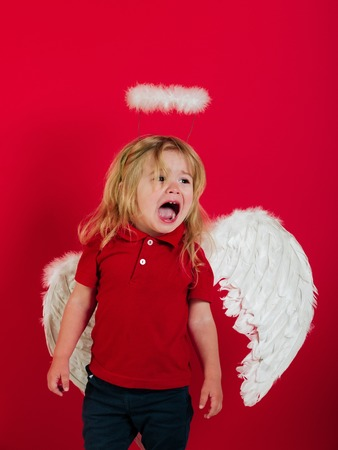adorable little angel boy with white feather wings and halo, crying kid with sad face and blonde hair on red background, cupid on valentines day holiday Stock Photo