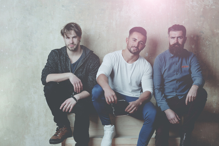 friends. people or men friends with different emotions on faces sitting on wooden stairs on beige wall. Unshaven caucasian models with stylish hair in casual clothes. Beards and haircuts fashion Imagens