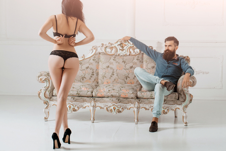 young couple of handsome bearded man in blue shirt and jeans with pretty cute girl or woman in black lingerie with sexy buttocks on luxurious vintage couch or sofa on white background