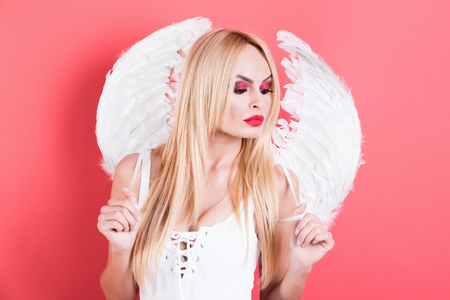 angel girl portrait, sexy blonde woman with wings, angel with long hair and bright makeup on pink background