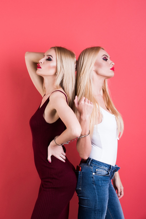 women in handcuff, fashion cloth posing on pink background, pretty blonde girl friends, twins sisters having bright makeup, homosexual and gay Stock Photo