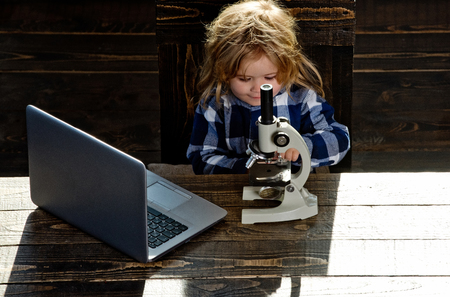 educational concept, a boy student studying at his workplace with microscope and laptop