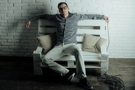 narrator: singer. handsome young man in fashionable glasses, checkered shirt and pants sit on wooden bench on white brick wall background with professional mic or microphone