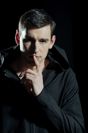 man. elegant handsome man in stylish coat on black background, holding finger near mouth has thoughtful face, shady business