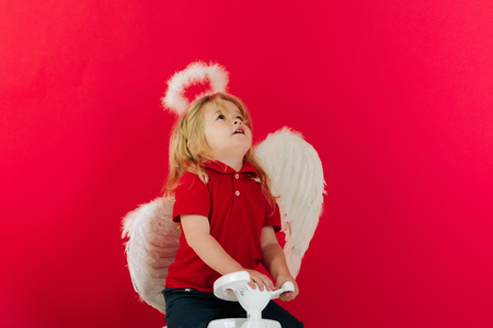 angel happy boy on red background for valentine greeting, beautiful cupid has an idea