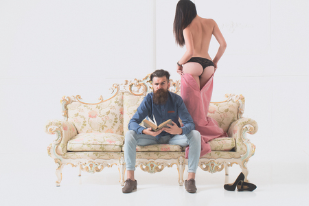 young couple of handsome bearded man in blue shirt and jeans with pretty cute girl or woman in black panties topless with sexy buttocks on luxurious vintage couch or sofa near shoes on white