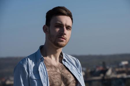 ひげとスタイリッシュな髪、ヘアカットでポーズをとるモデルまたは若く、ハンサムなセクシーな白人男男、日当たりの良い夏の日、青い空を背景 写真素材