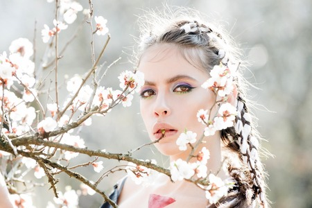 woman in white cherry or apricot spring flower blooming. pretty woman with fashionable make up on face and stylish hair sunny outdoor on natural background