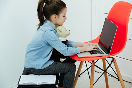 kid or cute, small, little girl with hair, ponytail, hugging adorable teddy bear and typing on laptop, computer, on orange chair in white room at home. Toys and technology