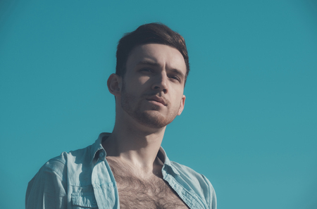 caucasian model or man with unshaven face and stylish hair, haircut, posing in unbutton shirt with hairy, naked chest on sunny, summer day, on blue sky background. Male beauty