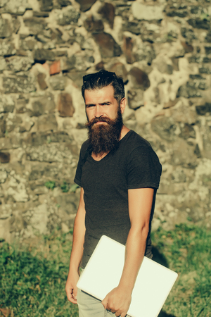Bearded man with long beard, brutal, handsome, caucasian hipster standing with grey laptop, computer, in black tshirt on sunny, summer day on stone wall. Nature and new technology Stock Photo