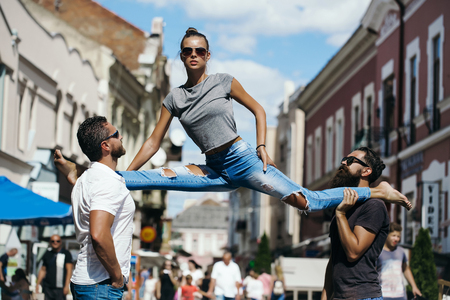 girl or pretty woman, fit model, in stylish sunglasses and blue jeans sitting leg split on shoulders of two bearded, handsome men on sunny, summer day on city street. Active lifestyle, friends Stock Photo - 78081956