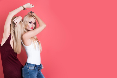 pretty women friends in handcuff or fashion twin girls with blonde hair on pink background, copy space
