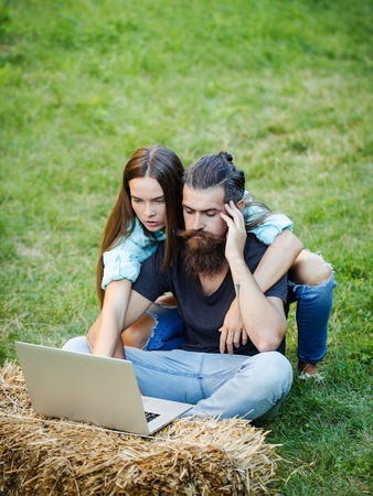 couple in love of bearded man, hipster, with beard and cute woman or pretty girl with long hair using laptop on hay bale on green grass on summer day on natural background. agile business Stock Photo