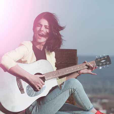 singing girl guitarist or pretty woman singer, musician with brunette hair playing guitar, musical instrument, on idyllic, sunny, summer day, outdoors on blue sky. Music and entertainment Stock Photo