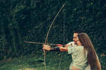 man and pretty woman or cute girl with long hair, archers or hunters, shooting with bow and arrow on summer day on green, natural background. Couple in love. Concentrate and aiming Stock Photo