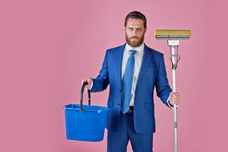 business and home, formal fashion, handsome man or businessman with broom and bucket on pink background, copy space Stok Fotoğraf