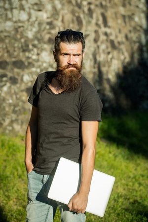 guy with long beard, hipster standing with laptop, computer, in tshirt on sunny, summer day on stone wall background. communication and new technology