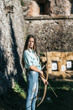 woman archer or pretty girl with long hair and blue jean clothes holding bow and arrow on sunny, summer day on blurred stone wall. Ambition, direction, target Stock Photo