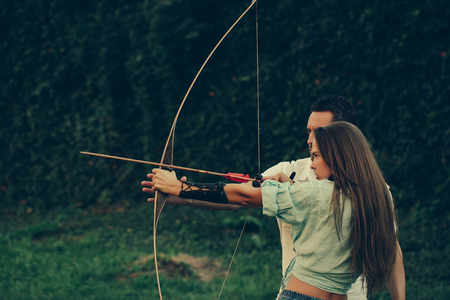 Couple in love, Concentrate and aiming, Cute girl or pretty woman with long hair and handsome man, archers or hunters, shooting with bow and arrow on summer day on green, natural background.
