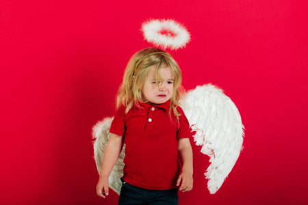 cupid. adorable little angel boy with white feather wings and halo, crying kid with sad face and blonde hair on red background, cupid on valentines day holiday Stock Photo - 78207546