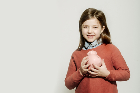 piggy bank in hands of cute, happy, small, little, girl, child in red sweater smiling on white background. Investment and money savings, copy space Banco de Imagens - 78207177