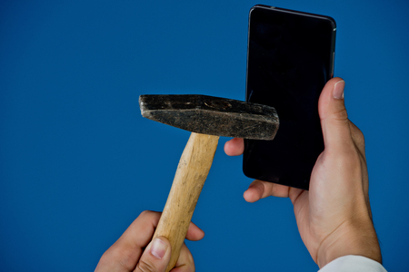 phone in hand crushed by hammer on blue background, copy space