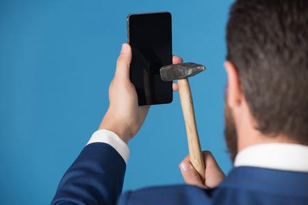 男がハンマー、青の背景に壊れた携帯電話でスマート フォンをクラックします。 写真素材