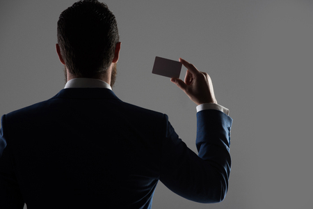 agent of insurance or man with business or credit card in formal outfit in shadow on grey background, back view, copy space, business ethics, shady business