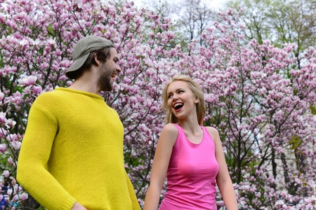 happy couple in love in spring magnolia flowers, smiling man and girl in garden with blossom tree outdoor on natural background